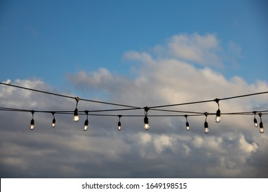 A string of outdoor lighting with on and off light bulbs hanging in the air, against a bright blue sky with clouds. Early morning feeling, selective focus on light bulbs.