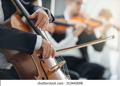 String section of classical music symphony orchestra performing, cellist playing on foreground, hands close up
