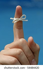 A string tied around a finger to remind someone of something.