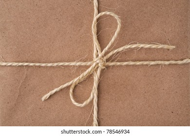 String tied in a bow, on a brown recycled paper package