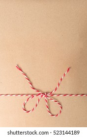 String or twine tied in bow on kraft paper texture.