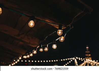 The string of vintage lights bulbs outside at night, lights on the background, selective focus