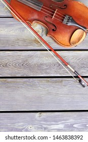 Stringed instrument of classical music. Vintage violin and fiddle stick on wooden background with copy space, top view.