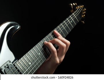 strings and guitarist hand playing guitar over black - shallow DOF with focus on hand