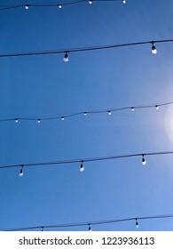 Strings of lightbulbs against a blue daytime sky
