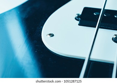 Strings on bass guitar. Close up. Vintage old retro bass in studio. Trendy cold style