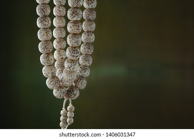 Strings of organic jewelry called rudraksha beads that are the material of malas,which is a rosary or used for prayer(japa) that are hung up with green background