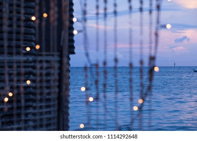Strings of seashells and christmas lights on a tropical island at dusk