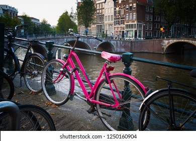 Strinking pink bicylce parked along a typical amsterdam canal
