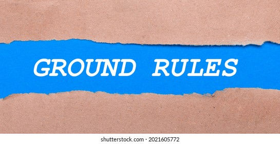 A strip of blue paper with the inscription GROUND RULES between the brown paper. View from above