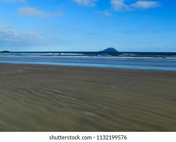 strip of dark sand with marks left by the waves during the high tide, and to the bottom waves and the island of the Montao de Trigo, under a blue sky with few clouds in the beach of Boraceia, no