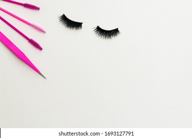 Strip lashes and lash extensions tools for a beauty salon in a flat lay style on a white background