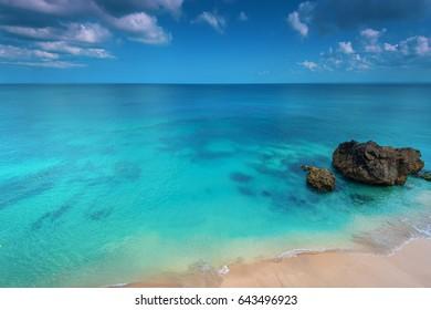 A strip of sandy beach and boulder against a calm sea surface
