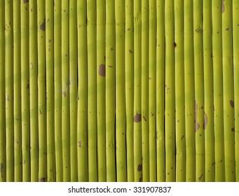 Stripe of shadow on yellow sprayed bamboo wall.