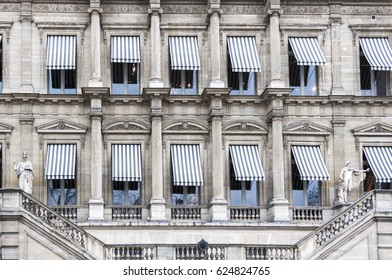 Striped awnings cover windows on an old building with ornate details in Paris France.