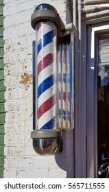 striped barbershop pole on exterior brick wall
