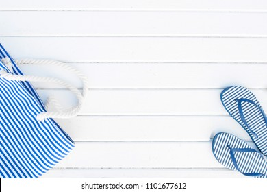 Striped beach bag and flip flops on a white wooden background