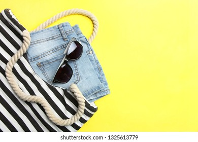 Striped beach bag, summer denim shorts and sunglasses on a yellow background. Concept summer vacation. Top view.