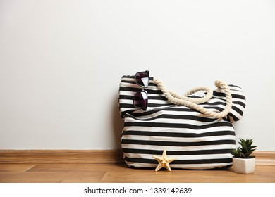 Striped beach bag with sunglasses and succulent on neutral background. Concept summer vacation. Copy space.