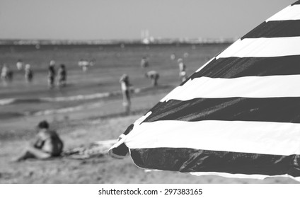 Striped beach umbrella and blurred people at background. Trouville-sur-Mer (Normandy, France). Selected focus on umbrella. Aged photo. Black and white.