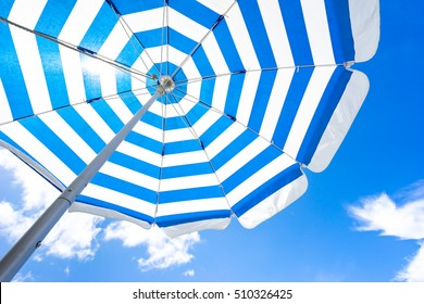 Striped beach umbrella on the beach.