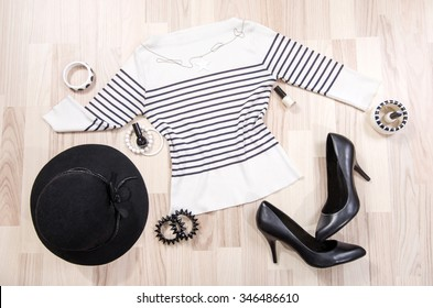 Striped blouse with accessories arranged on the floor. Woman black and white accessories, high heels, hat, necklace and nail polish lied down.