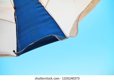 Striped blue white beach umbrella on the beach.