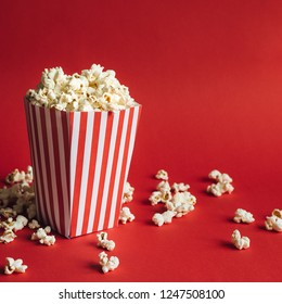 Striped box with popcorn on red background. Square format