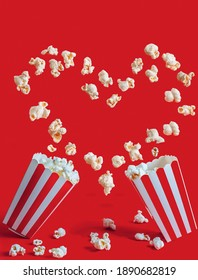 Striped box with popcorn on red background. Creative background for valentines day. Heart shaped popcorn levitation