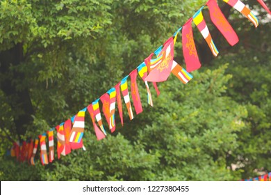 Striped buddhist flag near ancient stone temple, Roluos temple complex, Cambodia. Buddhist flag on way to Bacong temple. Religious festival celebration. Buddhist religion symbol. International flag