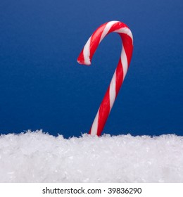 Striped candy cane on bed of snow ( Artificial ) with blue background.