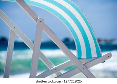 Striped deckchair blowing in wind on empty summer beach holiday concept