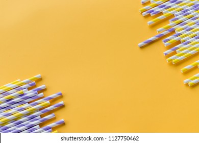 Striped drink straws of different colors in row isolated on yellow background. Minimalism concept. Pop art style. Flat lay with straws used for drinking water or soft drinks. Selective focus. Copy