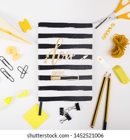 Striped exercise book with school supplies
