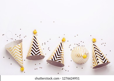 Striped golden cones hats and confetti on white background. Birthday holiday party concept.