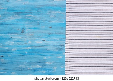 Striped napkin from right side of blue painted old board, abstract food background