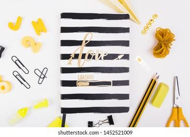 Striped notebook lying among school stationery