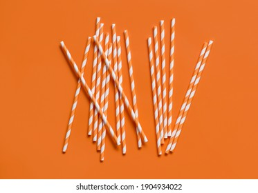 Striped paper drinking straws on orange background top view. Eco friendly and biodegradable