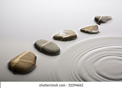 striped pebbles forming a curve in rippled water surface