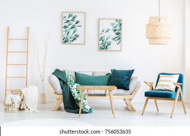 Striped pillow on blue armchair next to beige sofa with green pillows in cozy living room