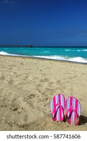 Striped Pink Sandals stuck in the Sand on Dania Beach, Florida with the Fort Lauderdale Pier in the Background. Plenty of Room for Copy in the Cloudless Blue Sky