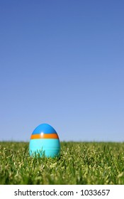 A striped plastic Easter egg on the grass with a blue sky - shallow DOF.
