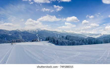Striped prepared ski slope on a background of mountain ranges and sky on ski resort in Carpathian Mountains