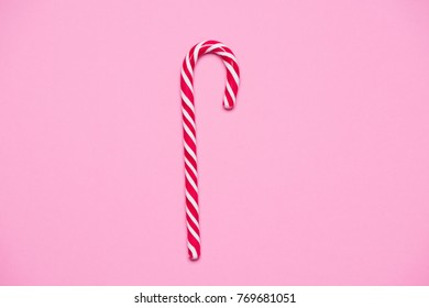 Striped red and white candy cande on pink paper background