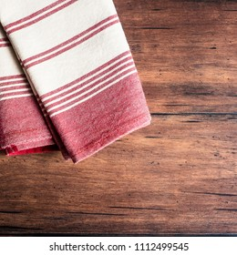 Striped red and white napkin on an old wooden brown background, top view. Image with copy space. Kitchen table with a towel - top view with copy space.
