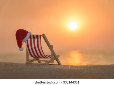 Striped red-white deckchair with christmas santa hat at ocean sandy beach during sunset, xmas or New Year's vacation in hot countries concept