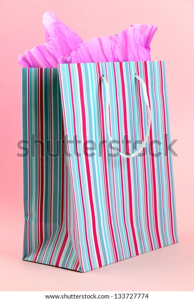 Striped shopping bag on pink background