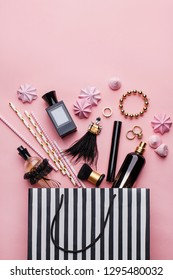 Striped shopping bag with various cosmetic products, perfume, jewelry and meringues on pink background. Top view, copy space