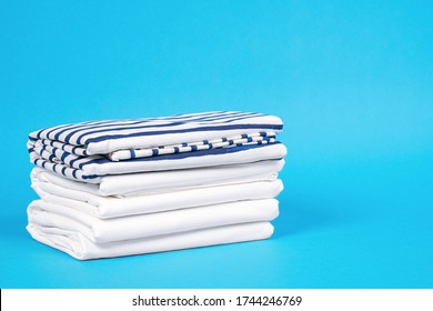 Striped and snowy white bed linen, neatly folded sheets on blue background. The concept of cleanness and proper storage organization. Indoors, copy space.