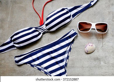 striped swimsuit and sunglasses on a gray wooden background.  Top view